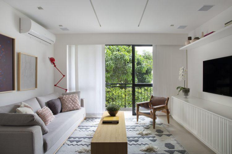Pequenas interferências para tornar os ambientes mais amplos em um apartamento no Leblon. Paredes brancas, rack tv com ripado branco e varanda com cortina em voal.