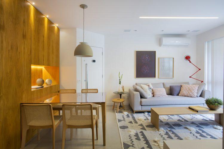 Pequenas interferências para tornar os ambientes mais amplos em um apartamento no Leblon. Sala com paredes brancas e parede lateral revestida em madeira