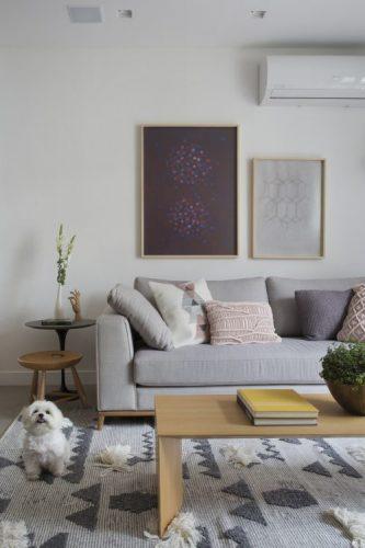 Pequenas interferências para tornar os ambientes mais amplos em um apartamento no Leblon. Paredes brancas, sofá cinza e um cachorrinho na foto.