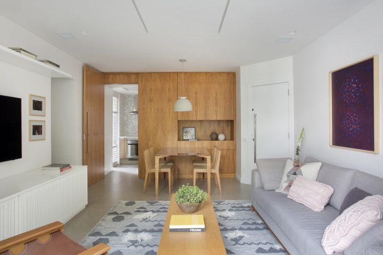 Pequenas interferências para tornar os ambientes mais amplos em um apartamento no Leblon. Sala clara e parede de funda da sala de jantar em madeira, com porta da cozinha camuflada.