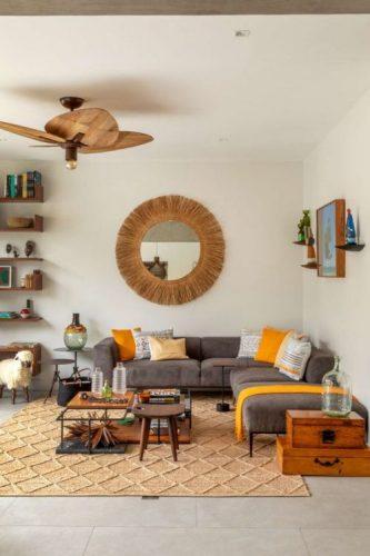 Sala com sofá cinza, almofadas amarelas, ventilador de teto em palha e espelho redondo na parede.