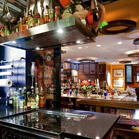 Paixões do arquiteto Chicô Gouvea, sua cozinha aberta para a sala. Coifa em cima do fogão, que fica no meio, repleto de tempero .