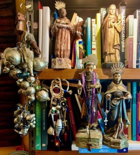 Paixões do arquiteto Chicô Gouvea. imagens de santos na prateleira de livros.