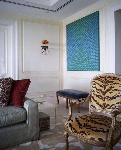 Estampa animal print na decoração, poltrona com estampa de zebra no ambiente com obras de arte contemporânea.
