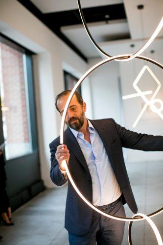 Michael Anastassiades, Designer do ano da Maison Objet. Foto do design segurando um circulo iluminado