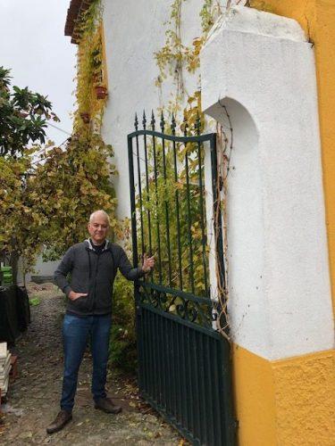 foto do arquiteto Maurico Nóbrega em Portugal, no portão de ferro em uma casa.