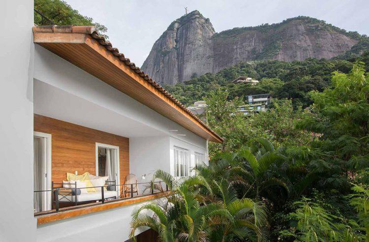 Foto de um casa com cantinho de leitura na varanda, com vista para o Cristo Redentor e cercado de verde