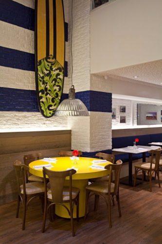 Restaurante com mesa amarela, parede de tijolinho pintado de branco com listras azuis e uma prancha de surf pendurada