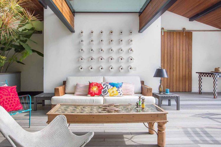 Foto de uma sala, a parede atras do sofá com uma coleção de casinhas de passarinhos branco