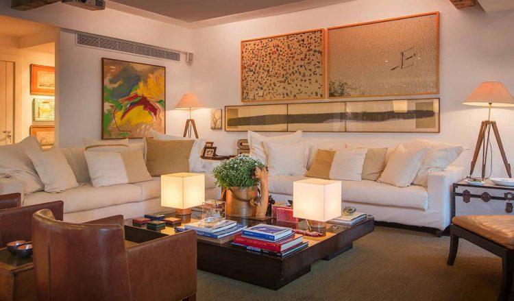 Sala decorada com sofás brancos, mesa de centro em madeira e obras de arte nas paredes.