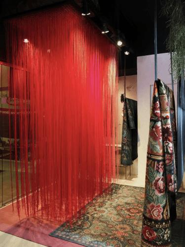 Vitrine de uma loja de tapetes, instalação com fios de lã na cor vermelha, vários fios pendurados um a um.