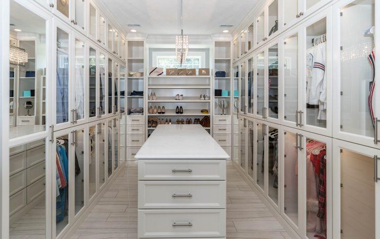 3 dicas para montar um closet funcional, closet grande com portas em vidro formando um L e no meio, um móvel branco com gavetas.