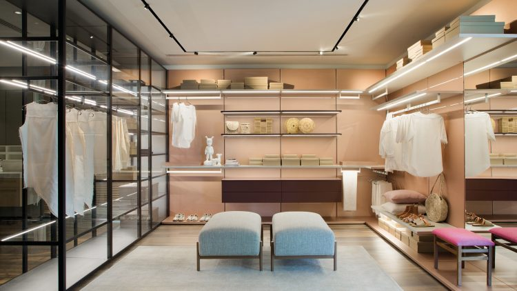 3 dicas para montar um closet funcional, closet grande com portas em vidro, partes abertas com prateleiras um banco no meio.