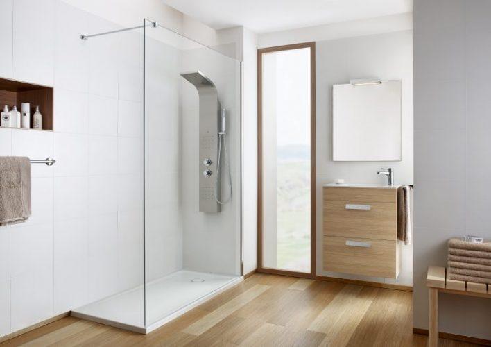 Banheiro com box transparente e coluna de inox no lugar do chuveiro