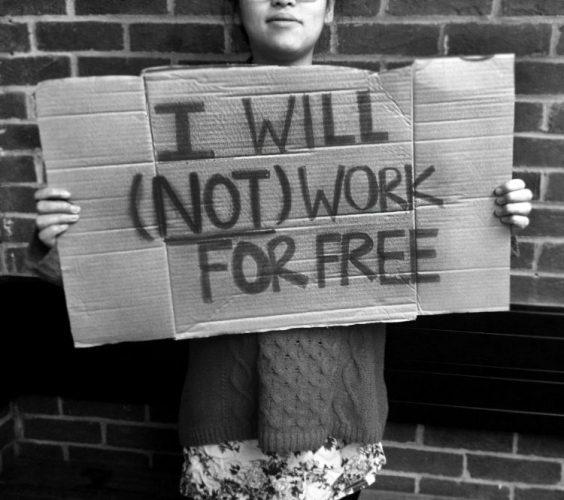 Jovem segura um cartaz feito de papelão escrito em inglês:  I will not work for free, tradução livre; eu não trabalho de graça.