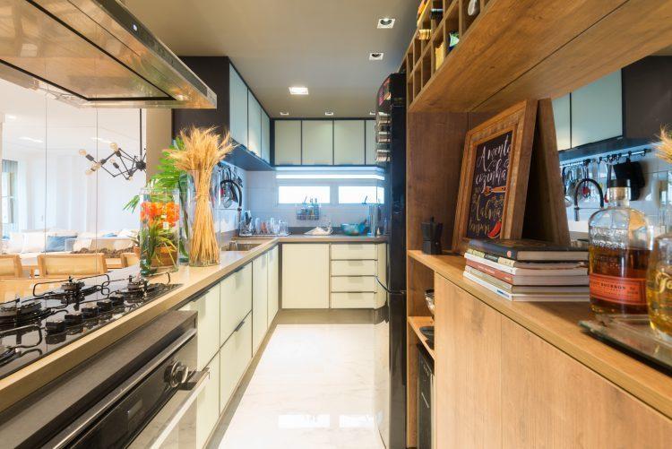 Cozinha comprida com a bancada do fogão aberta para a sala.