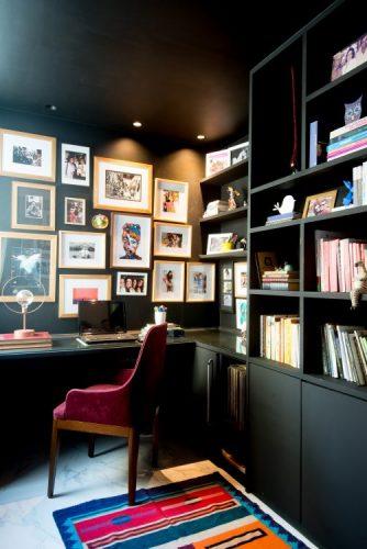 Escritório com todos os armários e paredes pintados de preto, poltrona na cor vinho na bancada