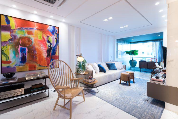 Sala com varanda integrada, tela colorida ao lado do sofá.