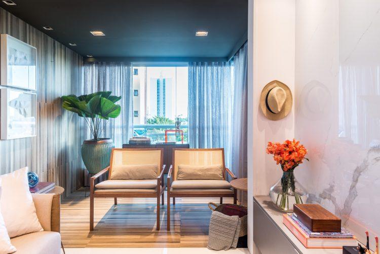 Sala com varanda integrada, piso em madeira e duas cadeiras ao fundo.