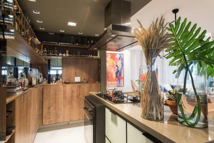 Cozinha integrada com armários  em madeira na parede lateral