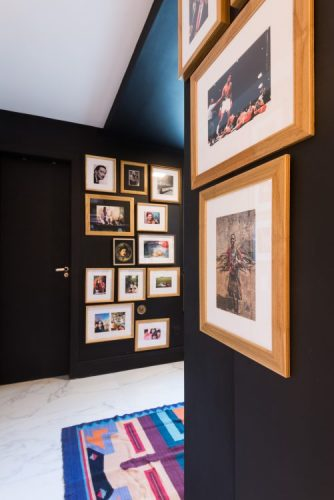 Corredor e portas pintado de preto abrigam coleção de quadros com a moldura em madeira