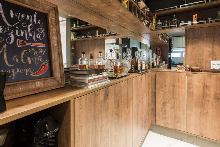 Armários em madeira compõe  o bar  que é integrado a cozinha