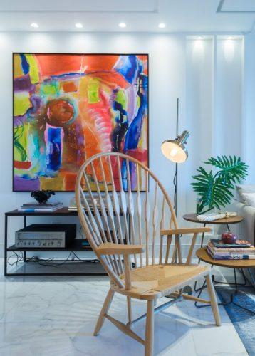 Tela colorida e cadeira de madeira com luminária de piso ao lado.