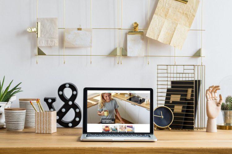 mesa de trabalho em madeira co um computador aberto em cima.