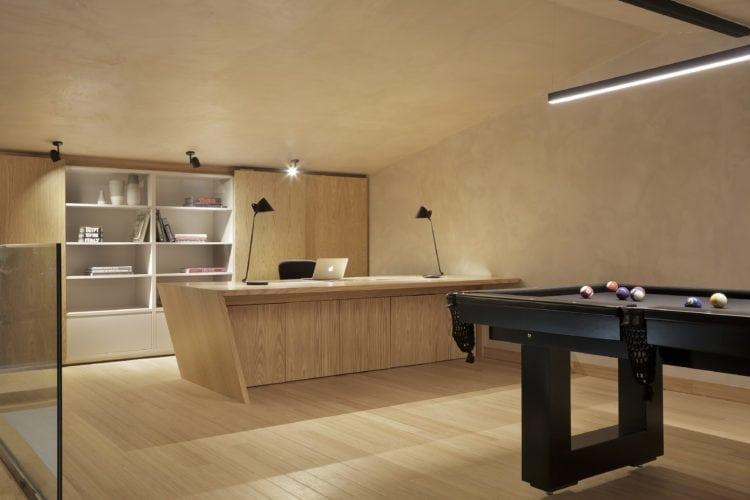 Espaço grande com mesa de bilhar e mesa em madeira clara com computador