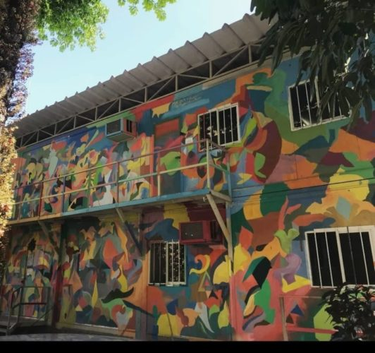 Dois contêineres empilhados e com a faixada pintada estilo grafiti