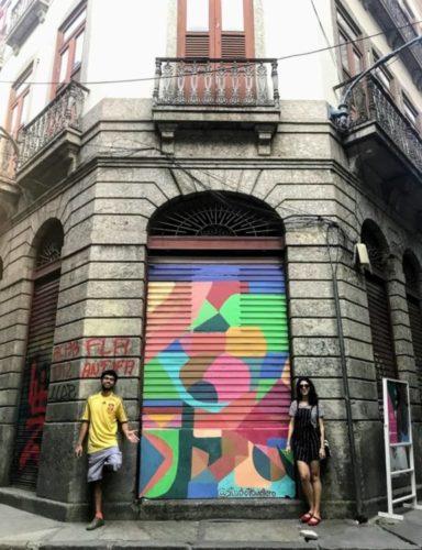 Porta pintada, estilo grafiti,  de um casario antigo no Rio e os artistas ao lado, um homem e uma mulher.
