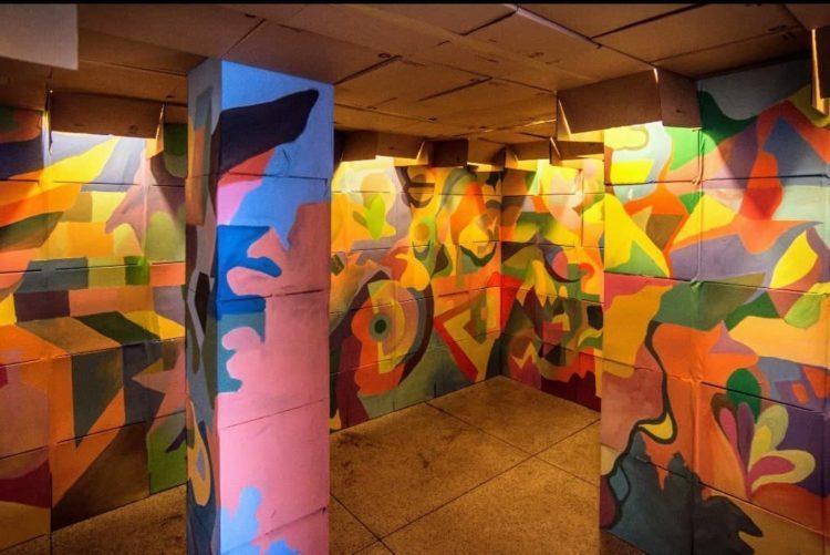 Instalação artistica, 700 caixas pintadas , coloridas com desenhos geométricos  de papelão empilhadas criando um túnel