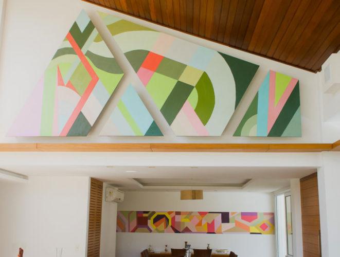 Telas em formatos diferentes coloridas com desenhos geométricos na parede  interior de uma casa