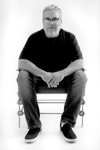 Foto preta e branca  do design, com barba e óculos sentado em uma poltrona