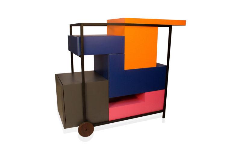 Foto de um carrinho de chá desenhado em pedaços coloridos, azul ,laranja e rosa