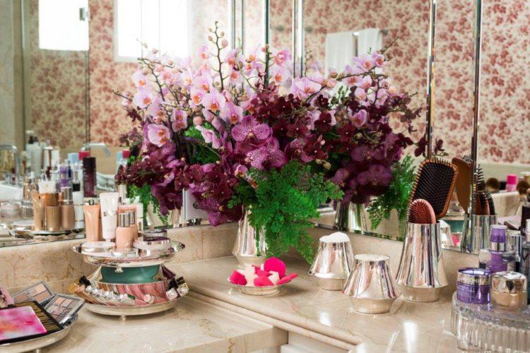 Em parceria com Anna Carolina Bassi-St. James lança coleção Femme. Bancada de banheiro em mármore com peças em prata, vasos de flores , bandejas para maquiagem