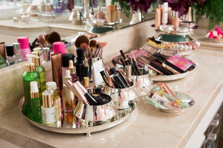 Em parceria com Anna Carolina Bassi-St. James lança coleção Femme. Bancada de banheiro com varias bandejas e potes em prata para arrumar maquiagem.
