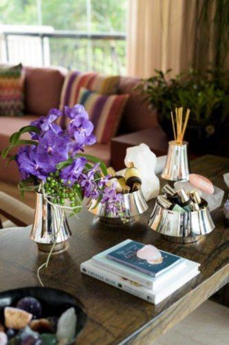 Em parceria com Anna Carolina Bassi-St. James lança coleção Femme. Em cima de uma mesa de madeira, potes em prata com flores, óleos e pedras
