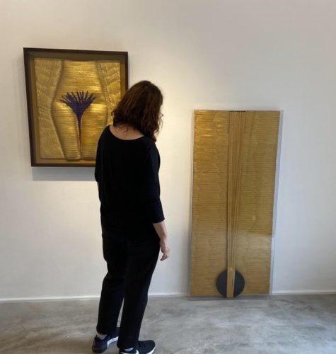 Foto da artista plastica Anna Paola Protasio vestida de preto e de costas arrumando a sua exposição