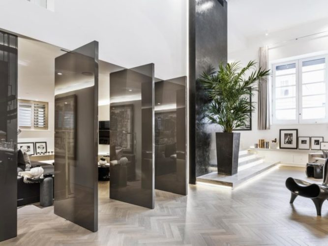3 Portas pivotantes pintadas de marrom abertas para um sala de tv