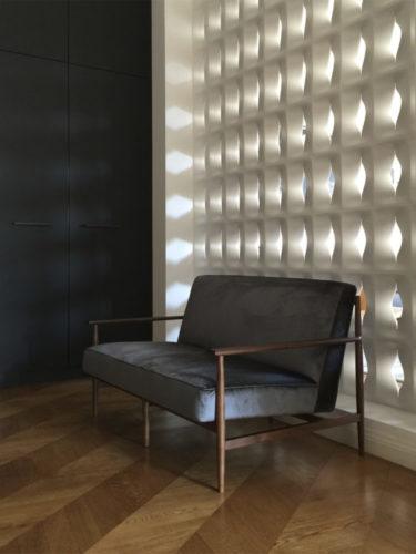 sofá pequeno de dois lugares forrado em veludo molhado encostado na parede de cobogó branco