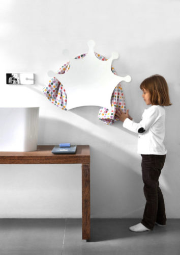Menina pendurando uma toalha de bolinhas coloridas do toalheiro em formato de coroa branca