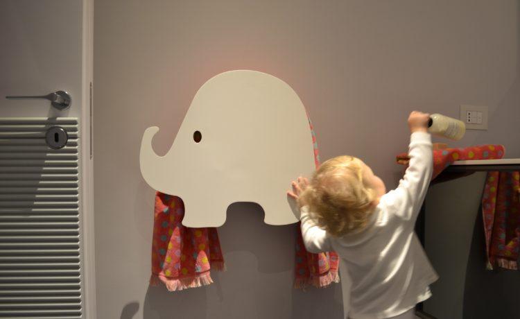 Foto de um criança ao lado de um toalheiro em formato de elefantinho branco