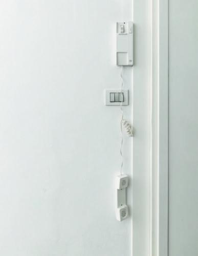 como enxergam a quarentena os principais fotógrafos de arquitetura do mundo. Foto de uma parede branca, com um interfone branco com o fone caído.