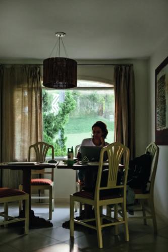 como enxergam a quarentena os principais fotógrafos de arquitetura do mundo. Em uma sala de jantar, uma mulher sentada com o computador aberto