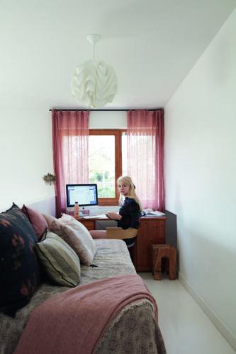 como enxergam a quarentena os principais fotógrafos de arquitetura do mundo. Quarto com paredes brancas, cortina rosa na janela com uma menina adolescente sentada na cadeira em frente ao computador
