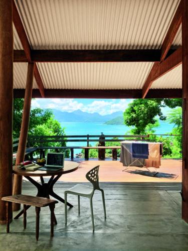 como enxergam a quarentena os principais fotógrafos de arquitetura do mundo. Foto de uma varanda coberta, com uma vista incrível para o mar. Na varanda um varal de pé com toalhas secando ao sol.