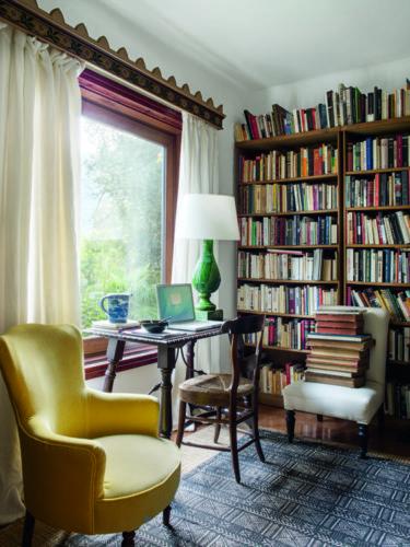 como enxergam a quarentena os principais fotógrafos de arquitetura do mundo. Foto com uma estante de livro, em frente a janela, uma escrivaninha com uma cadeira e um abajur verde.