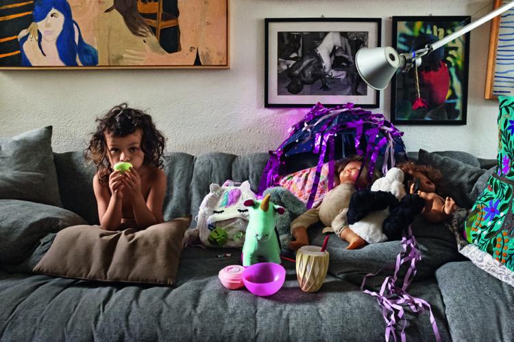 como enxergam a quarentena os principais fotógrafos de arquitetura do mundo. Foto de uma criança, menina, em um sofá cinza com brinquedos ao lado