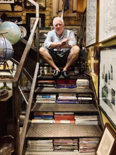 Estante com arte. Foto do arquiteto Chicô Gouvea sentado em uma escada, que entre os degraus estão vários livros